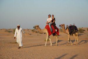 una coppia in cammello guidati da un beduino nel deserto