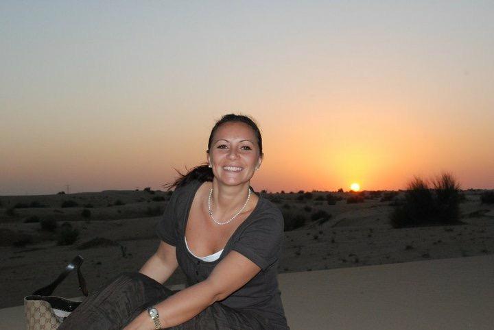 donna seduta sulle dune nel deserto di dubai al tramonto