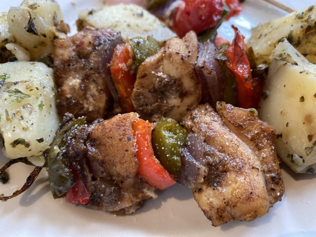 piatto di spiedini di pollo con verdure grigliate e patate lesse
