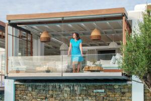 donna con abito turchese, affacciata al terrazzo di un hotel di lusso.