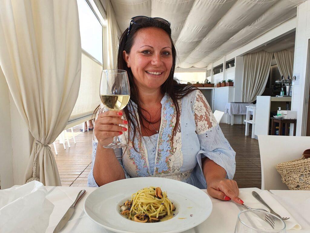 ristorante da Gianni torre mozza salento- donna che mangia un piatto di pasta con in mano un calice di vino