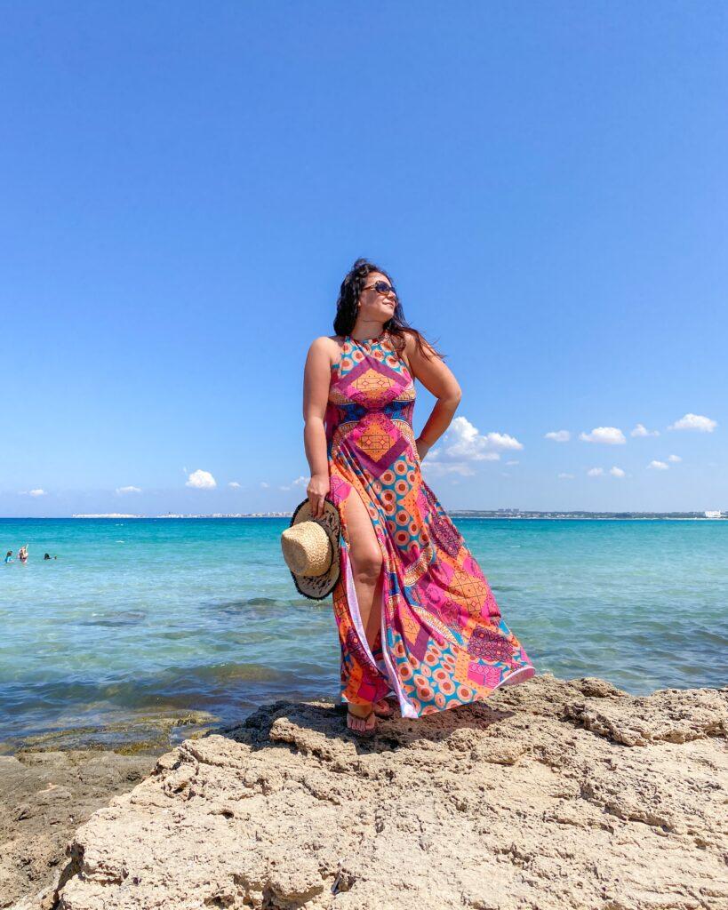 Lido Punta della Suina-donna in posa su uno scoglio con dietro il mare azzurro.