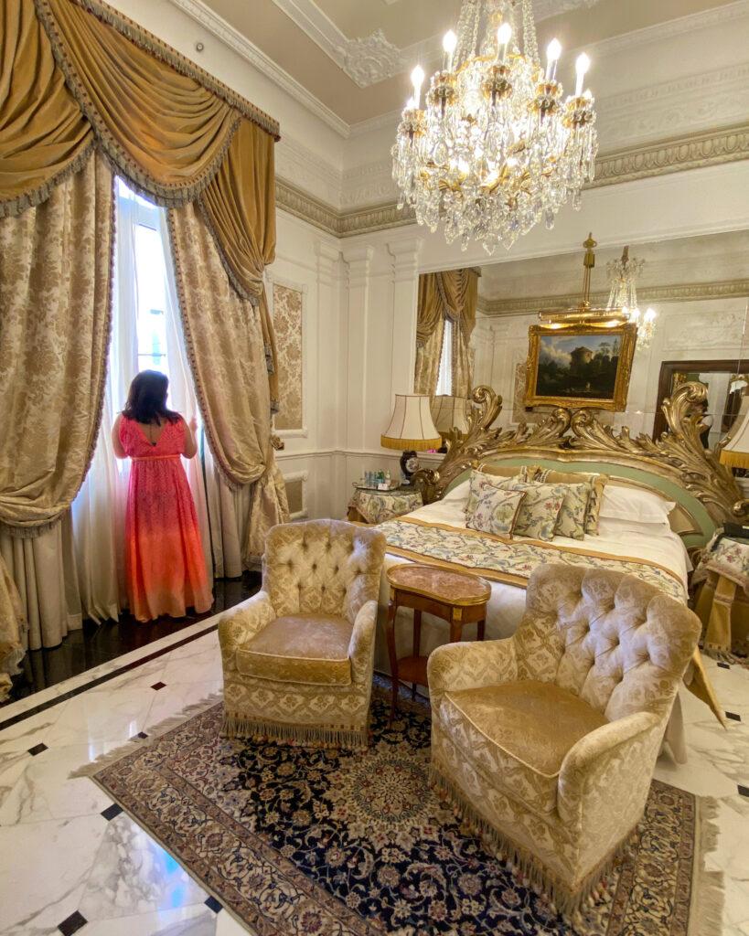 donna affacciata alla finestra di un'elegante camera arredata con mobili Luigi XVI