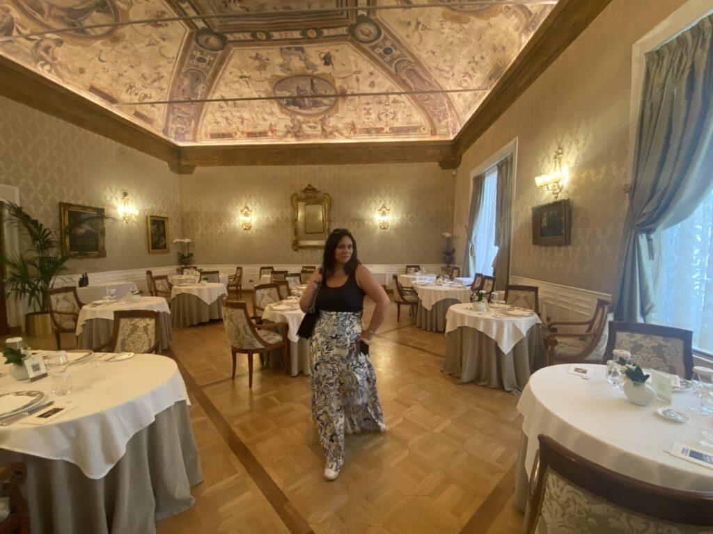 Immagine del ristorante I Carracci con affreschi originali sul soffitto e una donna in posa tra i tavoli
